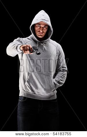 Young man with hood over his head holding a gun symbolizing crime isolated on black background