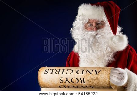 Santa Claus reading a list of good boys and girls. Christmas.