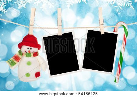 Blank photo frames and snowman hanging on the clothesline over blue christmas background