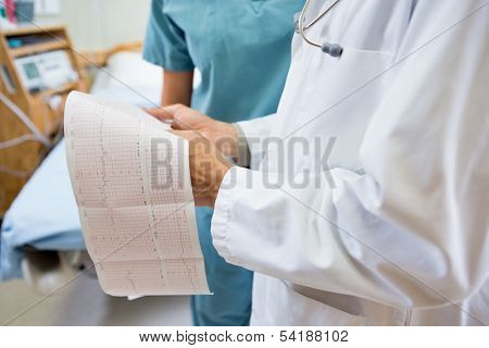 Midsection of male doctor and nurse with fetal heartbeat report in hospital