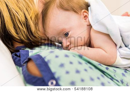 Closeup of adorable newborn babygirl lying on mother in hospital