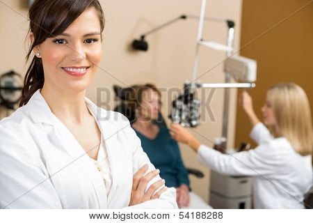 Portrait of female optometrist with colleague examining patient in background