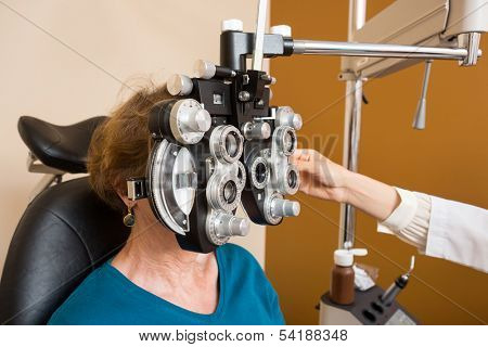 Senior woman undergoing eye examination with phoropter in store