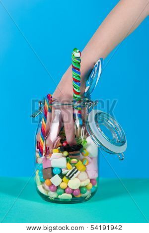 Young woman with many unhealthy sweets or candy in Studio, she have a sweet tooth and grabbing some goodies out of a glass