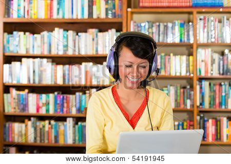 Student - Young woman in library with laptop and headphones learning and smiling