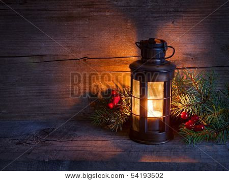 Cristmas lantern  in night on old wooden background. focus on the wick candles