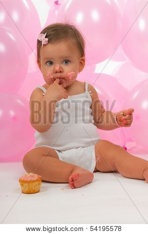 Birthday baby eating her birthday cupcake