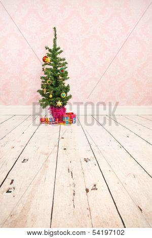 Vintage wall wooden floor and plinth with little Christmas tree and gifts