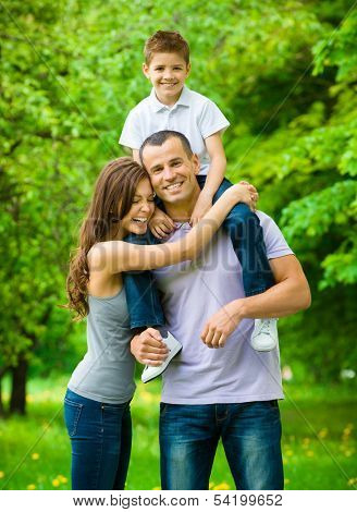 Happy family of three. Father keeps son on shoulders. Concept of happy family relations and carefree leisure time