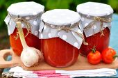 stock photo of vinegar  - Canned Tomato Sauce in Jars on a Chopping Board - JPG