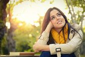 foto of daydreaming  - Pensive daydreaming woman relaxing in park on autumn - JPG