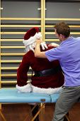 stock photo of stress relief  - male therapist massaging stressed Santa Claus - JPG