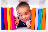 pic of peep  - Cute little boy peeping from behind shelf of colorful books - JPG
