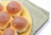 foto of bread rolls  - Fresh homemade white bread dinner rolls on a plate with napkin - JPG