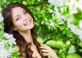 image of nearly nude  - Portrait of pretty girl near the flowered tree in the park - JPG