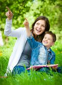 Mother and son with book sitting on green grass pointing hand gesture in park. Concept of happy fami