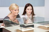 stock photo of jewel-case  - Two girls looking at showcase with jewelry at jeweler - JPG