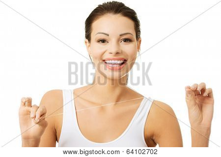 Beautiful young woman using dental floss, isolated on white