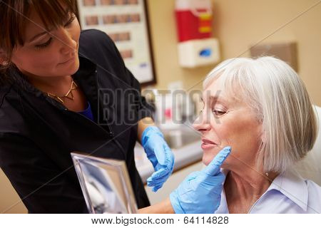 Female Client Looking In Mirror After Botox Treatment