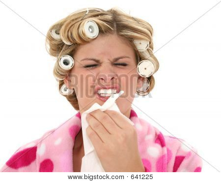 Young Woman In Rollers And Robe Sneezing