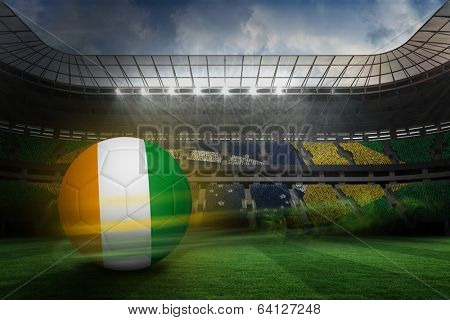 Football in ivory Coast colours against large football stadium with brasilian fans