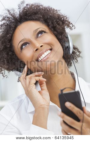 A beautiful mixed race African American girl or young woman looking up & listening to music on mp3 player and headphones