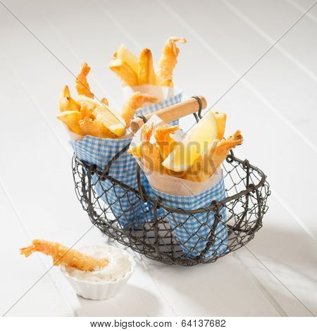 Fries and tempura prawns in a basket with tartar sauce on the side