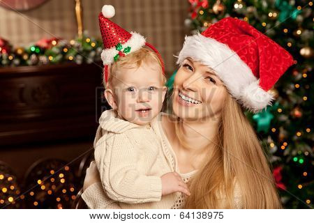Happy young smiling family near the Christmas tree celebrate New Year. Mom and kid at Christmas tree. Mother and child on Christmas Eve. Mummy and Baby.