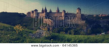 Beautiful old stone fortress. Fortification on the hill. Evening panorama. City Kamenetz-Podolsk, Ukraine, Europe.  Filtered image: vintage, grunge and texture effects