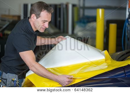 Car Wrapper Preparing Foil To Wrap A Vehicle