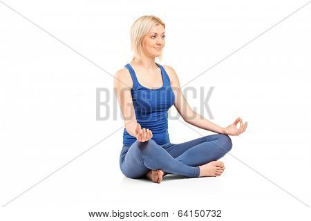 Woman meditating seated on the floor isolated on white background