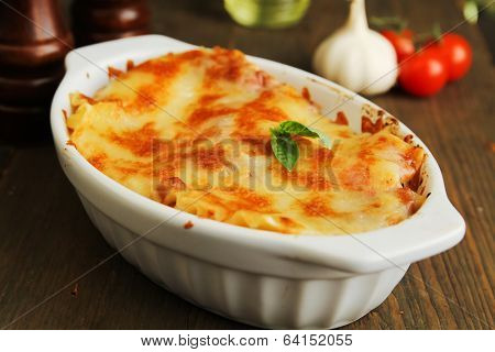 Fresh lasagna in a white container with basil