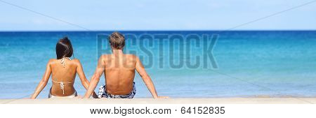 Beach travel banner - romantic couple relaxing on vacation enjoying ocean view together sitting in the sand embracing and hugging. Beautiful young multiracial couple, Asian woman, Caucasian man.