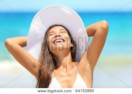 Beach woman enjoying sun tanning on travel smiling under blue sky. Cheerful beautiful bikini girl sun tanning having fun on tropical beach. Fresh laughing mixed race Asian Caucasian model on holidays