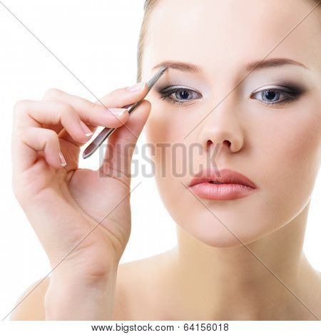 Beautiful young woman plucking eyebrows over white