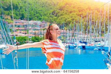 Cheerful female spending summer holidays, smiling woman with raised hands and closed eyes enjoys the sun, having fun in marina