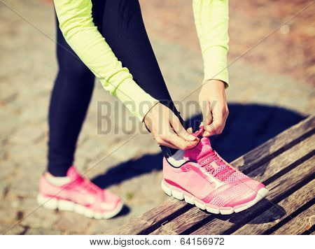 sport, fitness, exercise and lifestyle concept - runner woman lacing trainers shoes