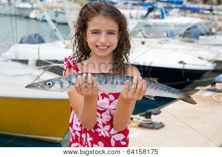 Happy kid fisherwoman with barracuda fish catch in Mediterranean marina