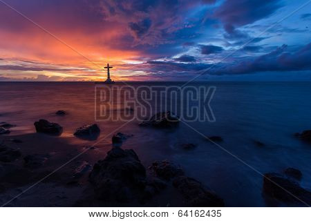 Catholic cross silhouette in a sunken cemetery at dusk, Camiguin island, Philippines