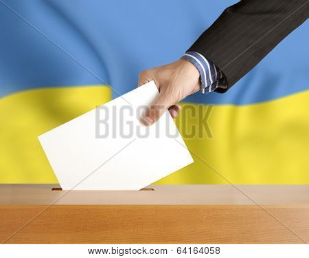 Male hand with ballot and box on Flag of Ukraine