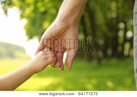 Parent Holds The Hand Of A Small Child poster