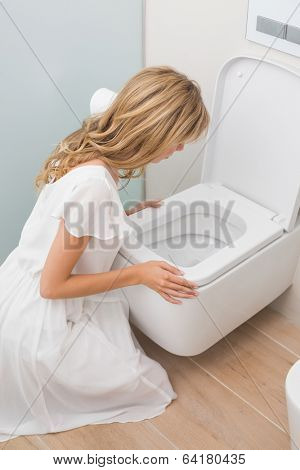 High angle view of a young woman about to vomit into a toilet