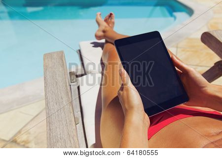 Relaxed Woman Using Digital Tablet By The Poolside