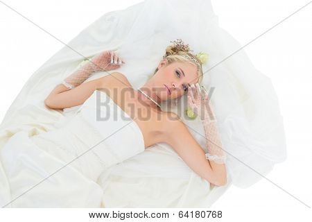 High angle portrait of sensuous bride lying against white background