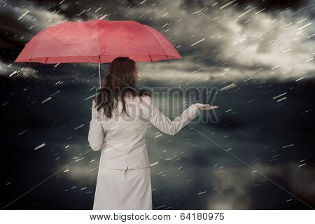 Businesswoman holding umbrella against cloudy sky with snow falling