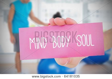Woman holding pink card saying mind body soul against trainer and client in fitness studio