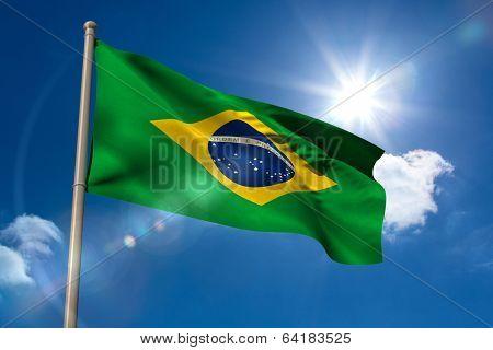 Brazil national flag on flagpole on blue sky background