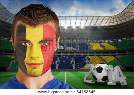Composite image of serious young belgium fan with face paint against large football stadium with brasilian fans
