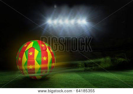 Football in cameroon colours against football pitch under spotlights