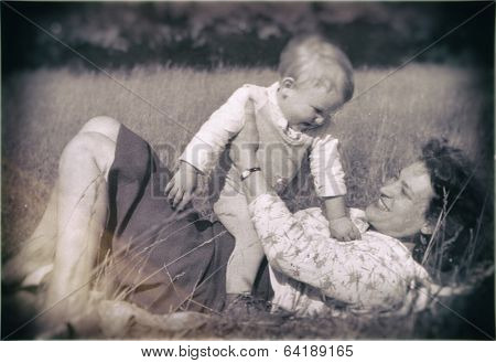 Poland, circa 1959:young mother with her baby boy playing in the grass, circa 1959